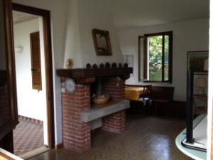 Casa 1-Mughetto: living-room with sofa and chimney