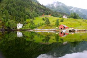Blick vom Fjord auf die Ferienhäuser (Pfeile)